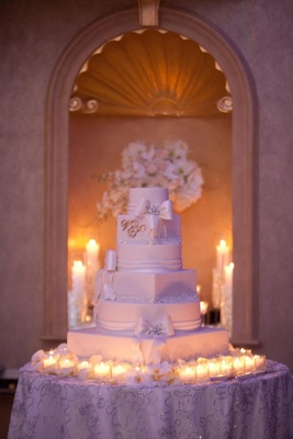 White wedding cake with crystals and fondant ribbons surrounded by candles