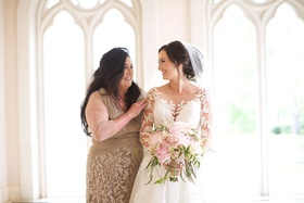 Bride in illusion wedding dress with pink green bouquet and mother of bride in tan dress lace detail