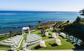 neutral tone ceremony seating on grassy yard facing the ocean view