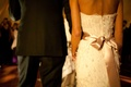 bride and groom back of white wedding dress with pink bow and black tuxedo