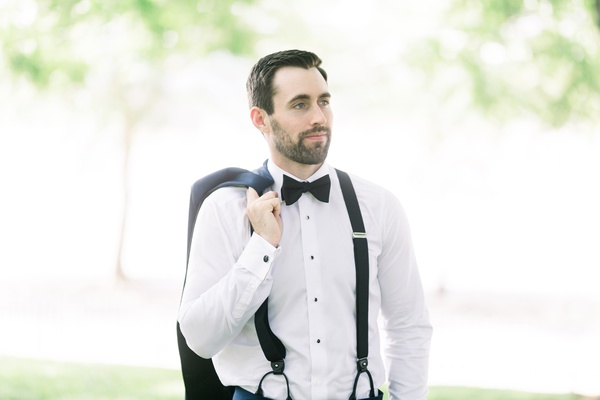 groom with stubble bears, carrying jacket over shoulder while wearing suspenders and bowties