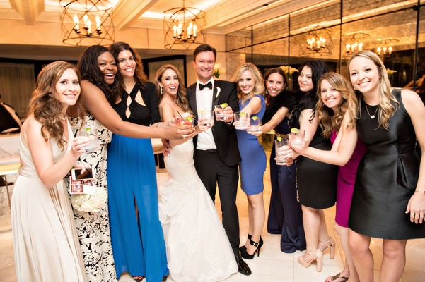 newlyweds hold cocktails out in posed photo with friends