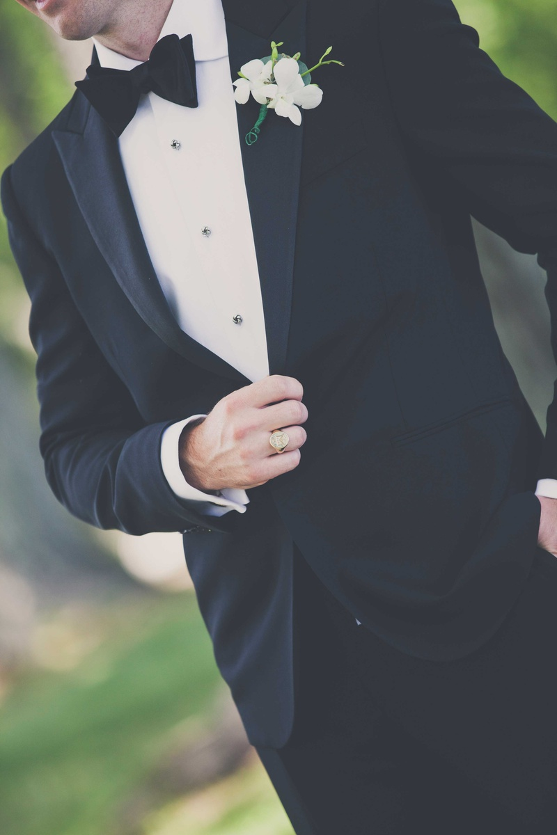 a close up shot of a grooms black tuxedo and his white and green boutonneire