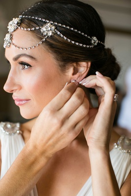 Bride putting on earrings French manicure headdress of jewels and flower details