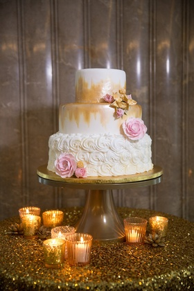 White wedding cake with rosettes covering one layer, gold brustrokes on the other two, pink & gold