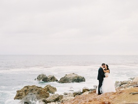 bride and groom share a kiss on a rocky beach before their oceanfront ceremony nuptials