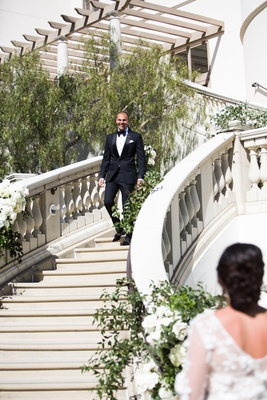 First look at monarch beach resort in dana point southern california groom walking down steps bride