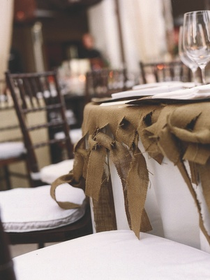 White and brown chairs around burlap tablecloth