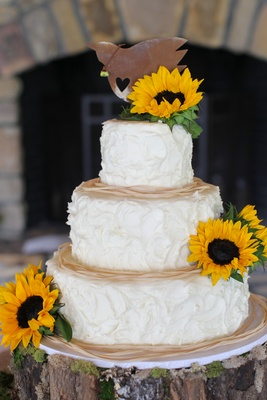 White cake with whipped frosting and fresh sunflowers