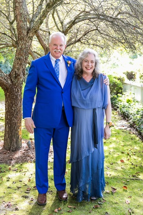 wedding portrait father of groom in azure blue suit and tie mother of groom in blue gown woods