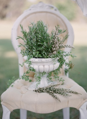 White stone urn with fresh herbs on tufted throne chair