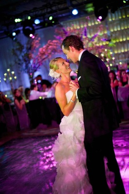 Bride and groom dance on purple dance floor at indoor reception