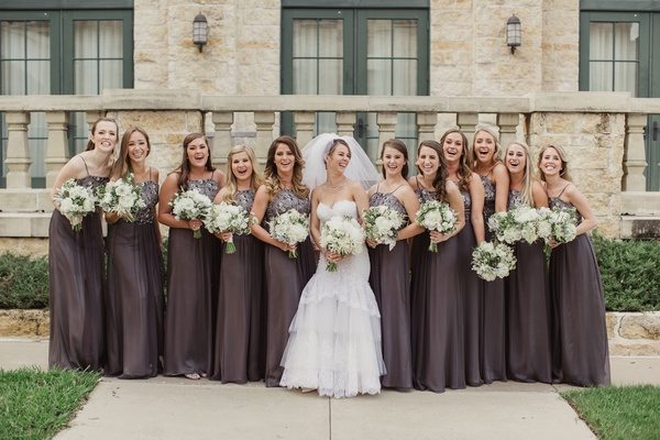bride and bridesmaids in Michael Faircloth grey long dresses with white bouquets and greenery