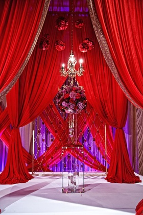 Indian ceremony with red drapes, chandelier, and red and purple floral arrangement