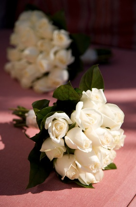Ivory rose nosegay with leaves tied with ribbon