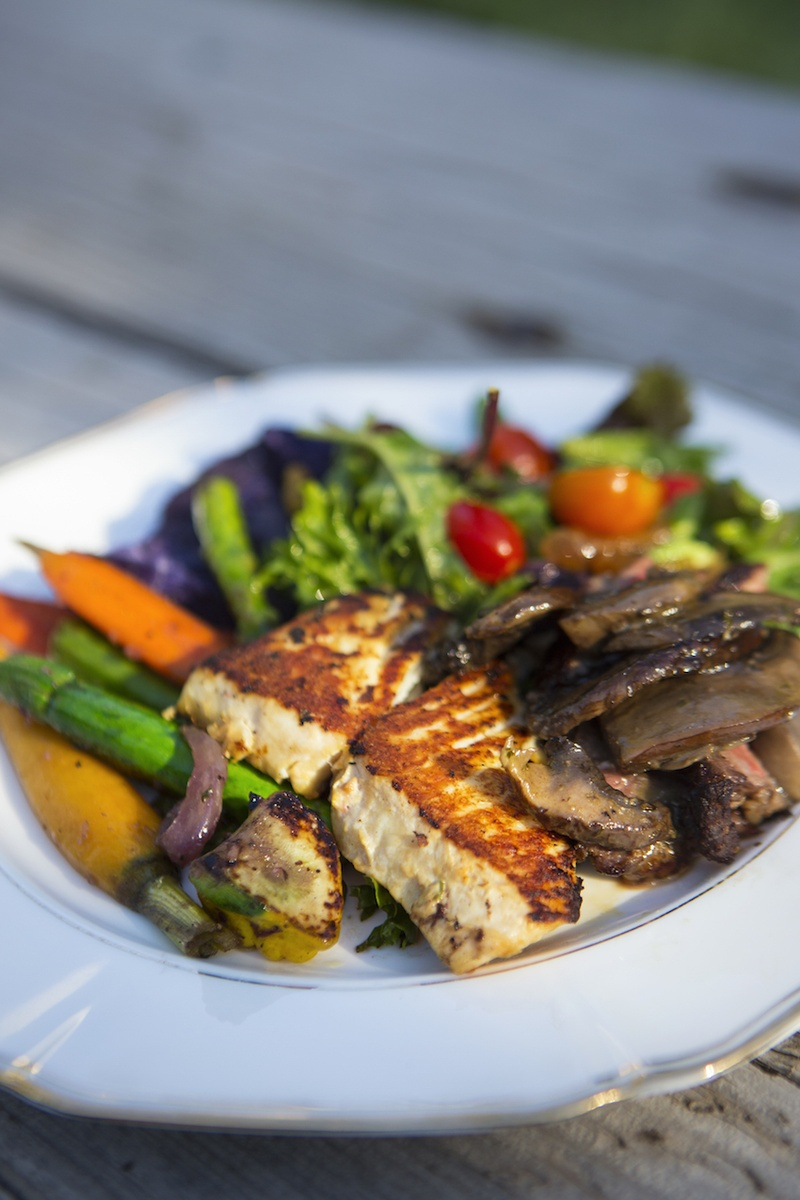 Salad and vegetables with grilled fish on plate