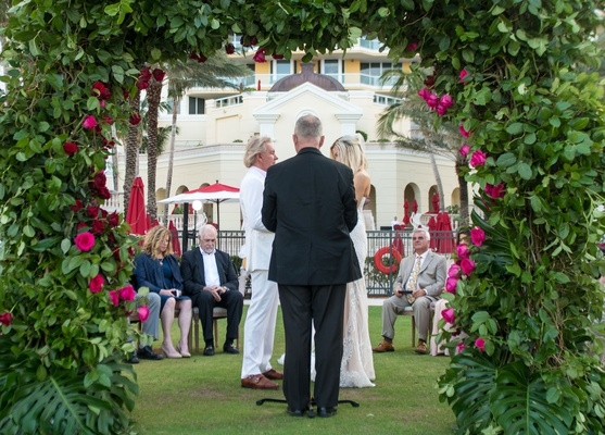 bride and groom with officiant at small ceremony acqualina resort and spa greenery arch pink roses