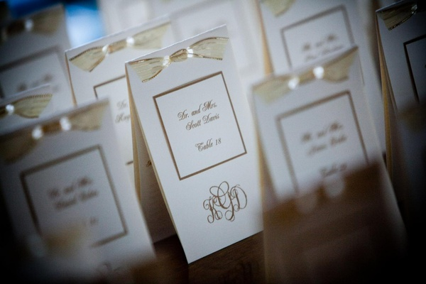 White and gold escort cards with monogram and bow