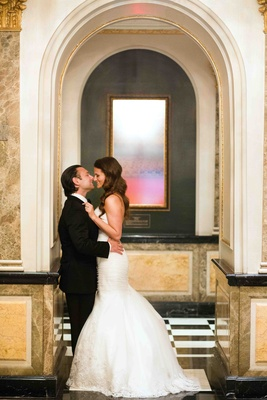 Groom kissing bride in Ines Di Santo trumpet gown