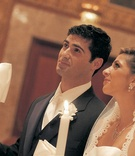 Bride and groom hold candles during Greek wedding ceremony