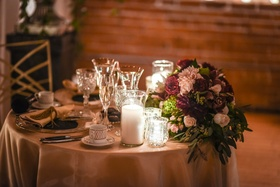small sweetheart table with burgundy and blush floral arrangement
