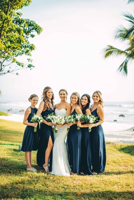 bride bridesmaids pose on beach blue white different dresses bouquets mexico punta mita