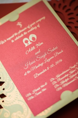 invitation for hindu wedding with red background and green sleeve with gold pattern