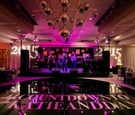 pink and purple uplighting in couples reception space with dance floor