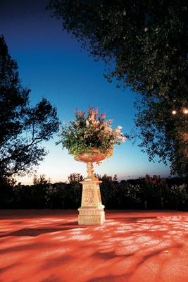 Classic stone urn full of greenery and flowers for a wedding reception