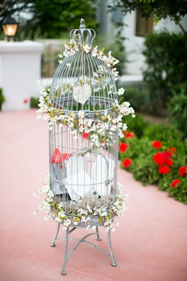 silver and white bird cage as wedding reception décor adorned with small white flowers and notes