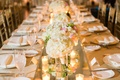 Floral centerpieces along the table on mirror runner white and blush flowers low flower arrangements