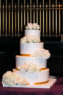 Four layer wedding cake with gold ribbon and fresh hydrangea and rose flowers on each layer