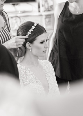 Black and white photo of bride getting headpiece put on