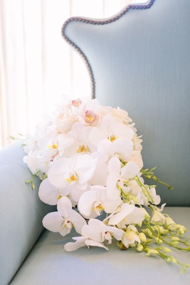 white orchids and ivory roses with cascading greenery on blue love seat