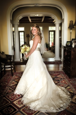 Bride in a strapless Vera Wang gown with a tan sash and bouquet of green flowers