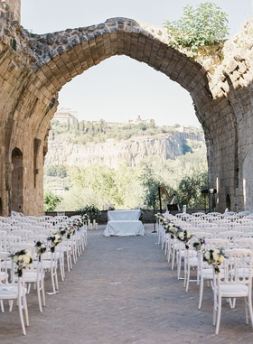 XII century Benedictine Abbey hotel countryside view umbria italy stone ruins white chairs purple