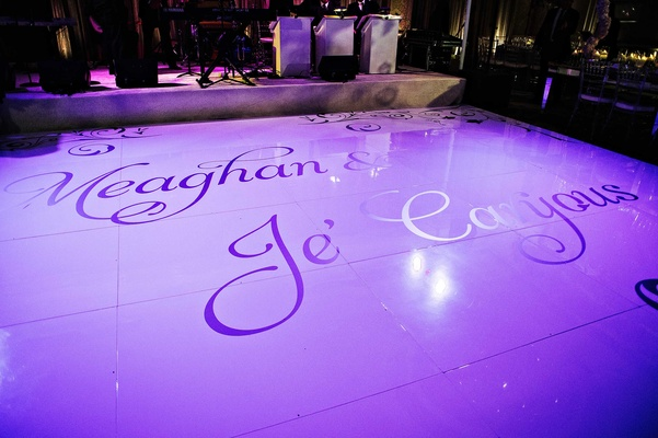 Custom dance floor at wedding reception with bright purple lighting and names