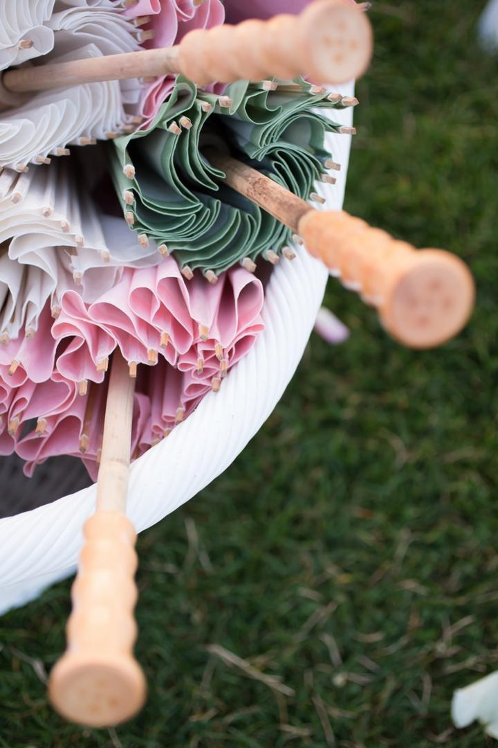 White bucket filled with green, white, and pink sun-umbrellas