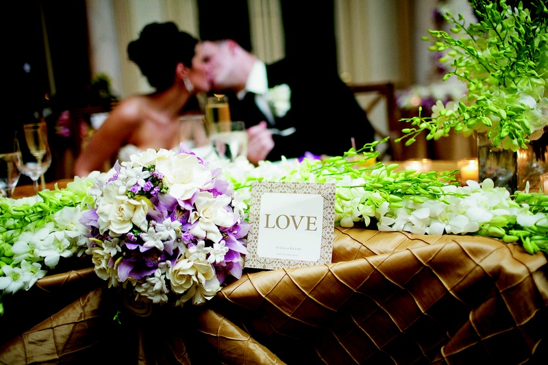 Wedding sweetheart table with golden tablecloths and white orchids