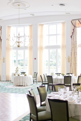 Wedding reception with green upholstered chairs, round tables at Garden City Country Club, NY