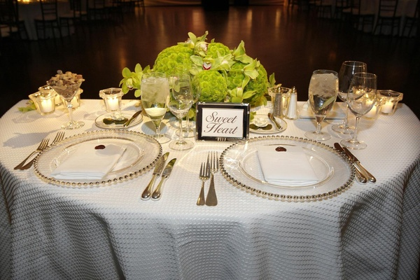 Half circle table with white tablecloth and green flowers