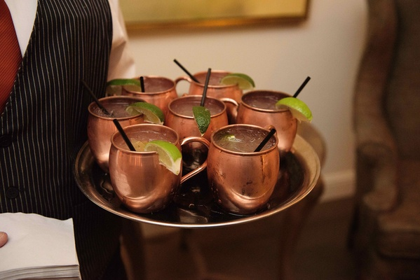 Copper Moscow mule mugs on tray with lime and black straws