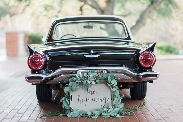 vintage getaway car for bride and groom with sign surrounded by greenery garland