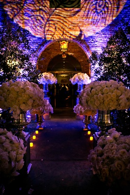 Purple lighting outside wedding venue with lush white rose flower arrangements leading to room