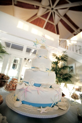 White cake with blue ribbons and seashell decorations