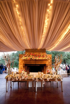Head table and sweetheart bench in front of tented fireplace