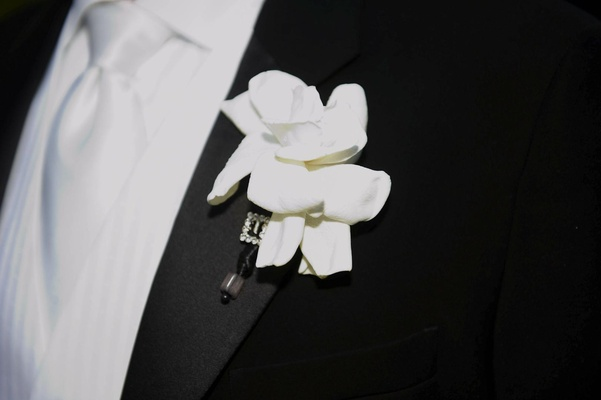White gardenia flower boutonniere on lapel with rhinestones