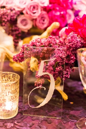 pink and purple floral centerpieces roses clear glass table number small candle
