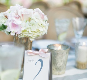 Table number in grey letters tied with pink ribbon