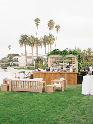 wedding reception outdoor bar with wood lounge area greenery tropical theme